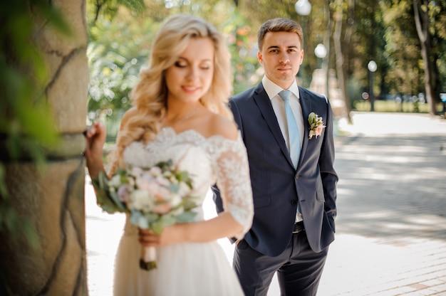 Sposo bello che sta sui precedenti della sposa