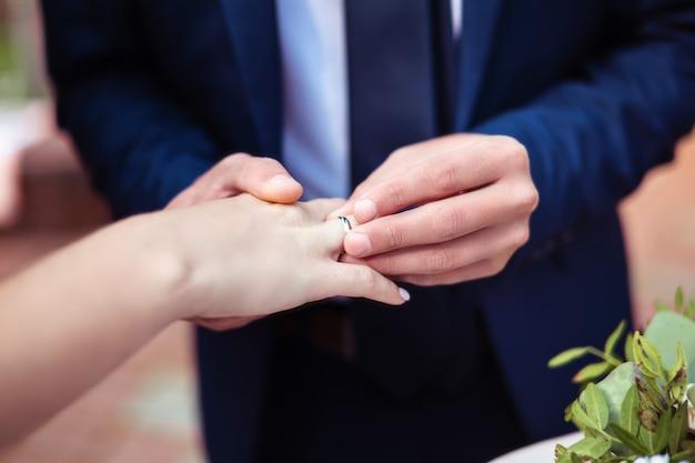 Sposo che mette fede nuziale sul dito della sposa