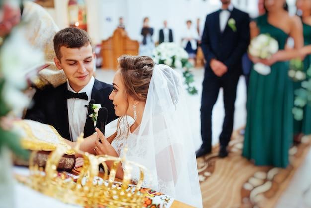 Sposo che mette un anello al dito della sposa durante il matrimonio