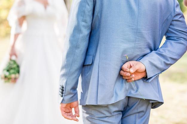 Sposo che nasconde il fiore dietro indietro per sorprendere la sposa il giorno del matrimonio