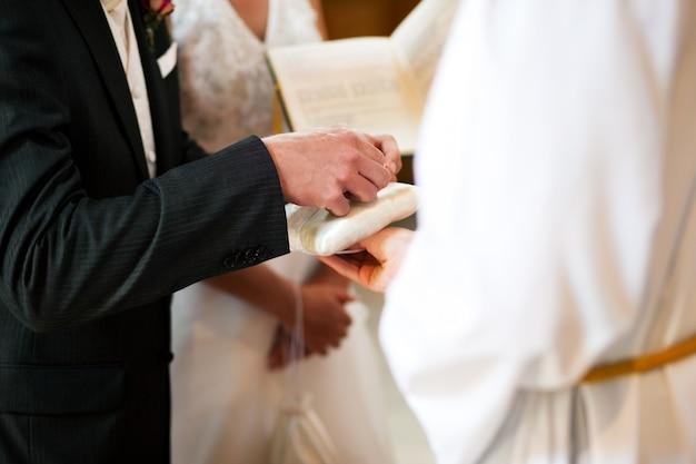 Sposo che prende gli anelli nella cerimonia di nozze