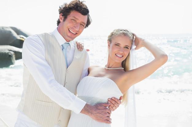 Sposo che tiene la sua nuova moglie sorridente mentre balla guardando la fotocamera