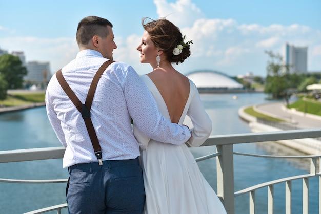 Sposo con la sposa sul ponte in città
