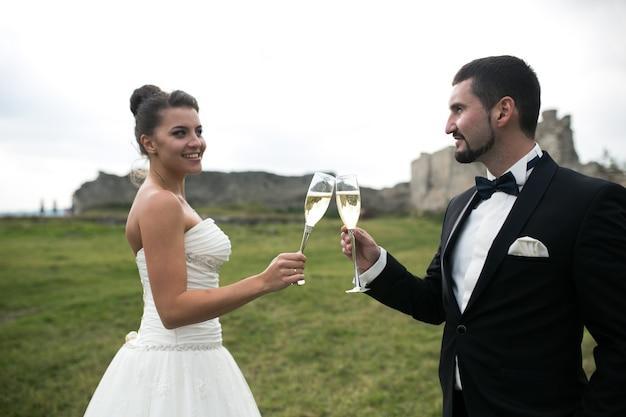 Sposo e sposa brindando con champagne
