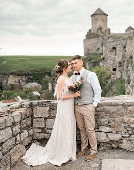 Sposo e sposa carina vicino all'arco di nozze dei precedenti del vecchio castello