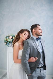 Sposo e sposa felici che posano con la bella decorazione dei fiori abbracciare delle coppie
