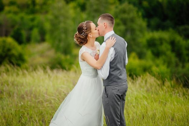 Sposo e sposa in abito da sposa alla natura. lo sposo bacia la sua sposa