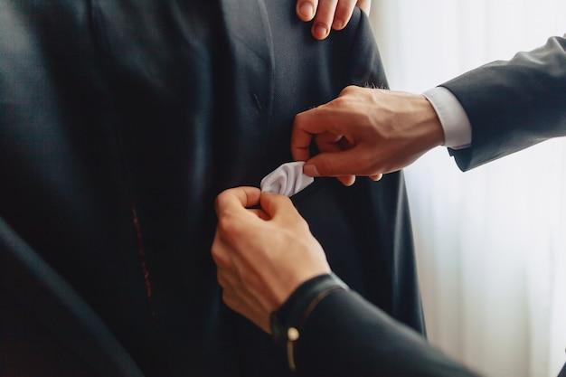 Sposo incontro, dettagli, giacca, scarpe, orologi e bottoni il giorno del matrimonio