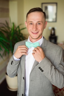 Sposo si prepara al mattino prima della cerimonia di nozze, indossando la giacca sulla camicia in camera.
