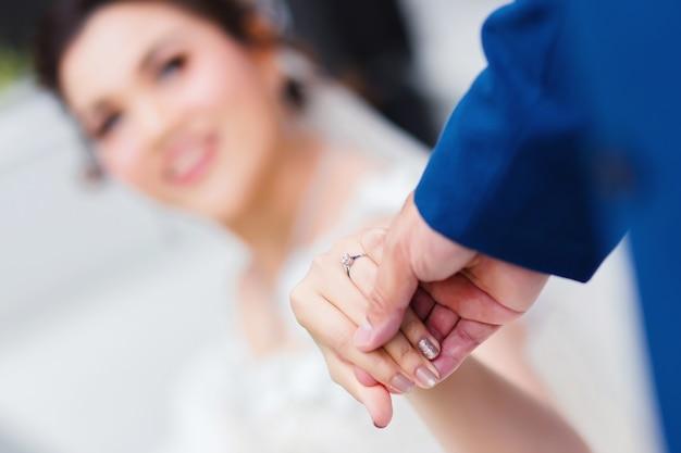 Sposo tenendo la mano della sposa per la cerimonia di nozze