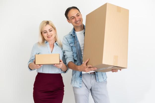Spostamento, casa e concetto di famiglia - coppie sorridenti che tengono le scatole di cartone