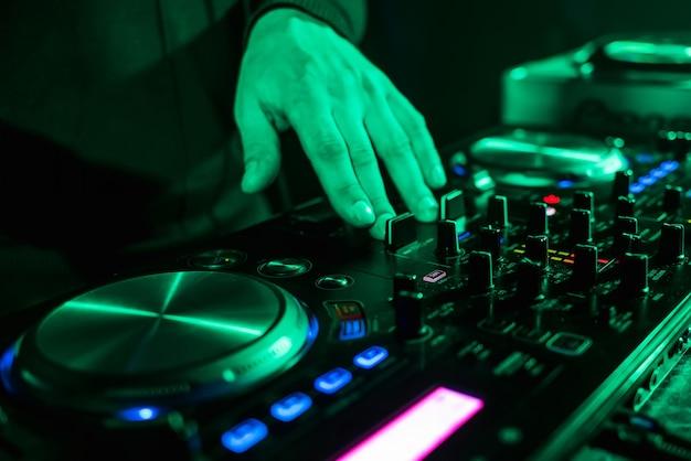 Spostamento manuale dei controller dj sul pannello di controllo della musica nel night club