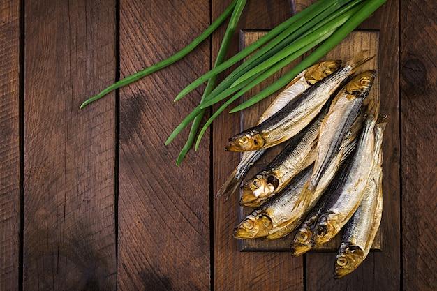 Spratto affumicato e cipolla verde su un tagliere. pesce affumicato. vista dall'alto