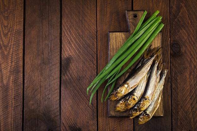 Spratto affumicato e cipolla verde su un tagliere su un fondo di legno. pesce affumicato. vista dall'alto