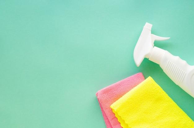 Spray detergente con stracci colorati su fondo menta