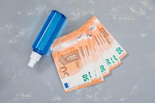 Spray disinfettante, banconote sul tavolo di gesso.