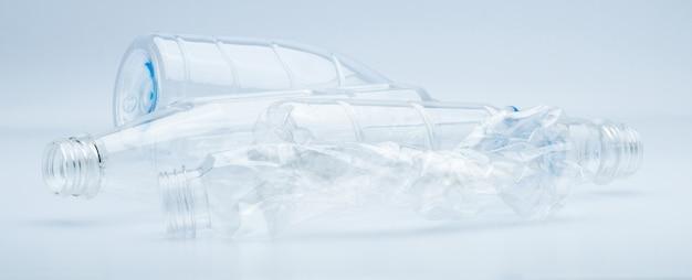 Spreco di bottiglie di plastica trasparenti isolate su fondo bianco con lo spazio della copia