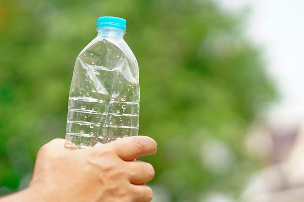 Spremere a mano la bottiglia d'acqua vuota preparare gettare nella spazzatura.