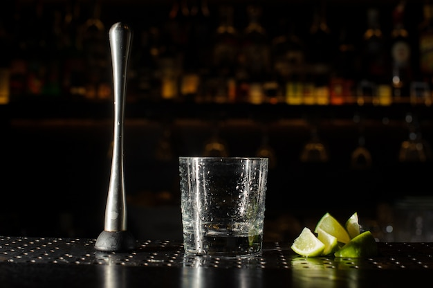 Spremiagrumi, bicchiere da cocktail e fette di lime sul bancone del bar