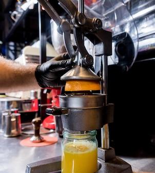 Spremiagrumi manuale in metallo. preparazione del succo d'arancia appena spremuto