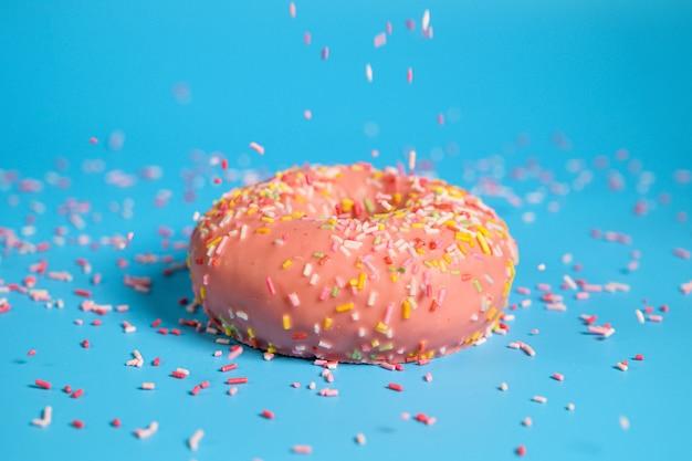 Spruzza cadendo dall'alto sulla gustosa ciambella alla fragola rosa. delizioso dessert su sfondo blu.
