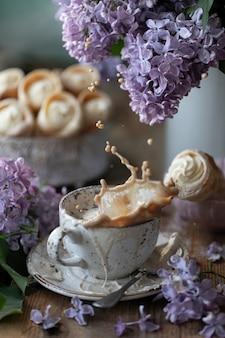 Spruzza in una tazza di cappuccino e corna di torta di pasta sfoglia con crema alla vaniglia in una scatola di metallo in primavera natura morta con un mazzo di lillà su un tavolo di legno