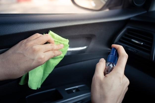 Spruzzare la superficie del disinfettante in auto