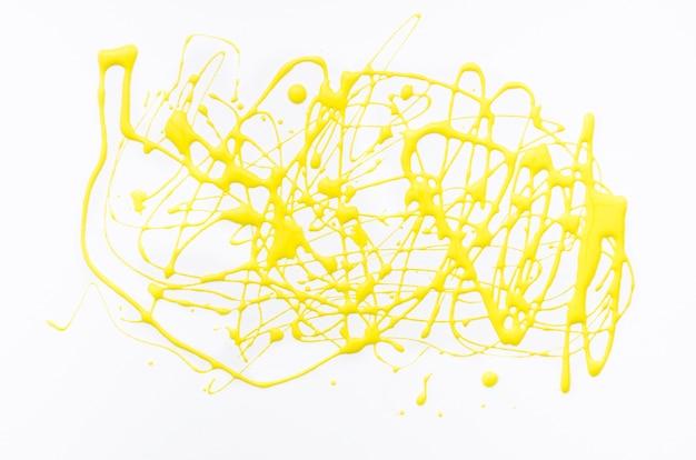 Spruzzata acrilica gialla su tela bianca