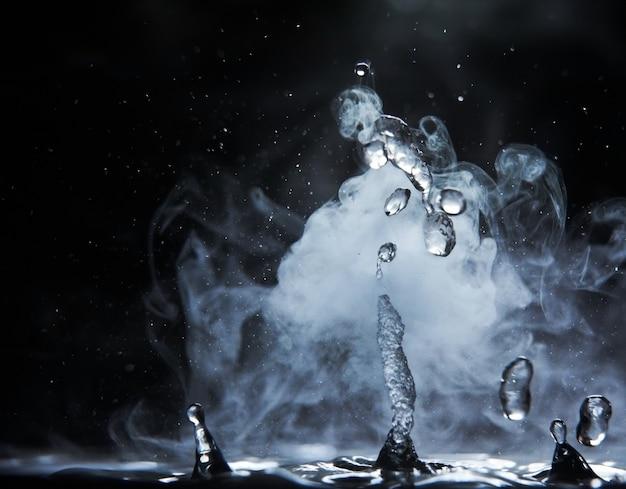 Spruzzata dell'acqua bollente con vapore sul primo piano nero del fondo