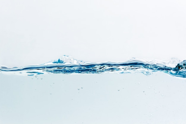 Spruzzata dell'acqua con le bolle di aria, isolata sui precedenti bianchi