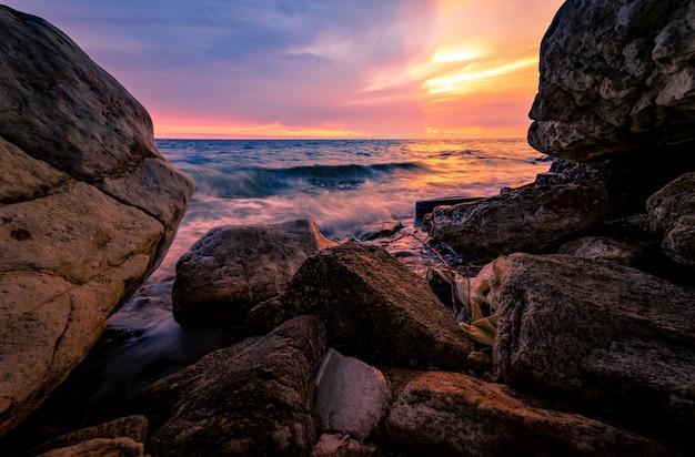 Spruzzata dell'acqua dell'oceano sulla spiaggia della roccia con il cielo rosa e dorato di tramonto. onda del mare che spruzza sulla pietra in riva al mare in estate. onda morbida.