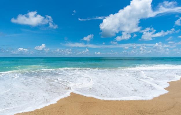 Spruzzata dell'onda dell'acqua di mare sulla spiaggia sabbiosa