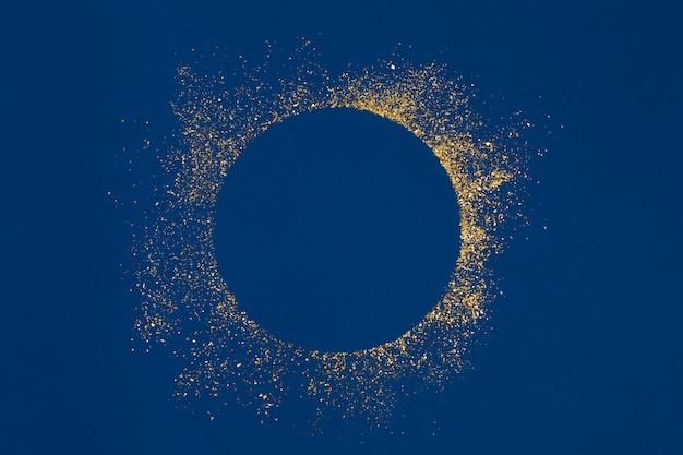 Spruzzata di glitter oro cerchio con centro vuoto su sfondo blu.