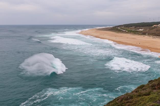 Spruzzata di onde nel vento sulle rive nazare.