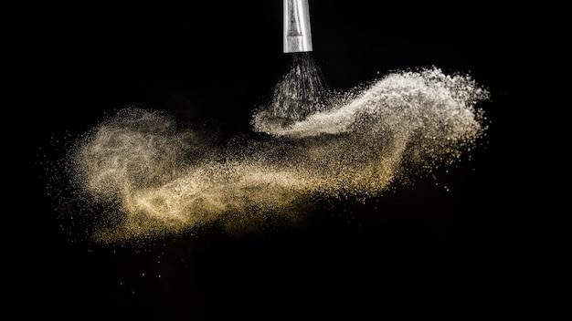 Spruzzata di polvere dorata e pennello per truccatore o blogger di bellezza in nero