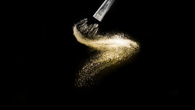 Spruzzata dorata della polvere e spazzola per il truccatore o blogger di bellezza nella priorità bassa nera