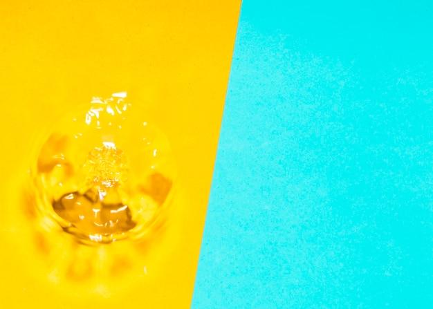 Spruzzata e bolle dell'acqua su fondo giallo e blu