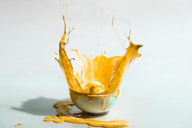 Spruzzata gialla della pittura e fondo astratto della tazza