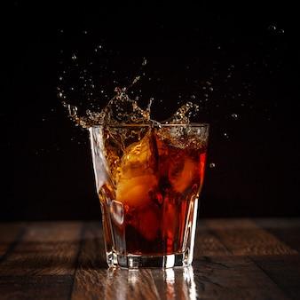 Spruzzata in bicchiere di cola con ghiaccio su sfondo grigio sfumato