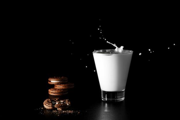 Spruzzata in bicchiere di latte e biscotto al cioccolato