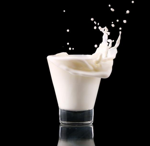 Spruzzata in un vetro con latte isolato sul nero