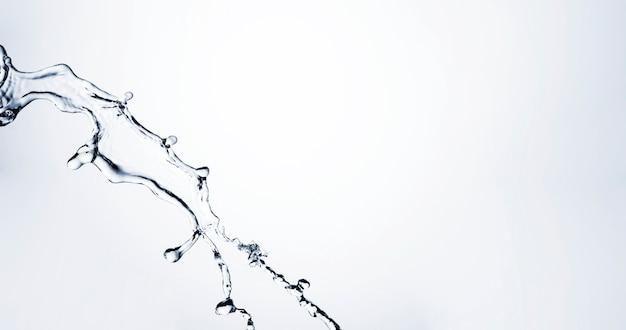 Spruzzata liquida trasparente del primo piano con lo spazio della copia