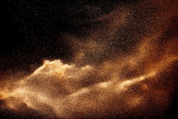 Spruzzata marrone della sabbia di colore contro fondo nero.