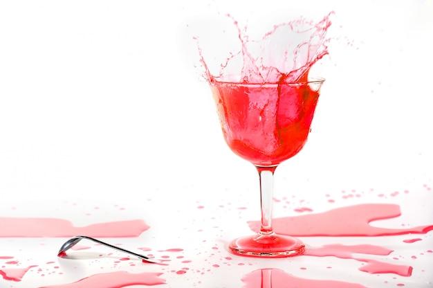 Spruzzata rossa della bevanda del cocktail dell'alcool su bianco