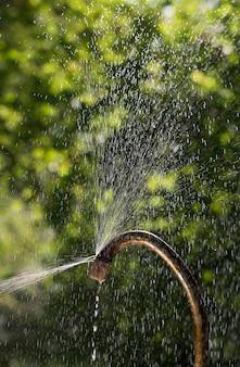 Spruzzi d'acqua dal vecchio rubinetto arrugginito e che è tappo chiuso