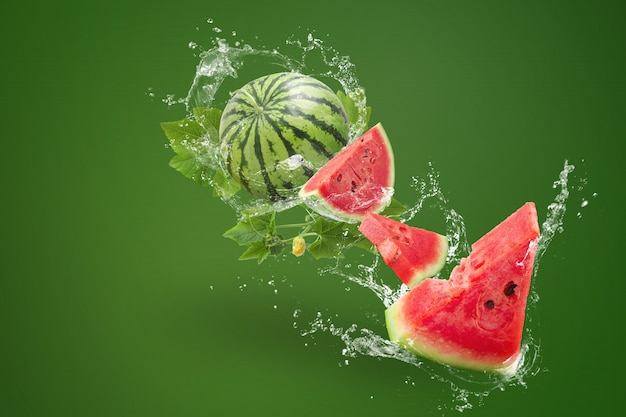Spruzzi d'acqua su affettato di anguria su sfondo verde