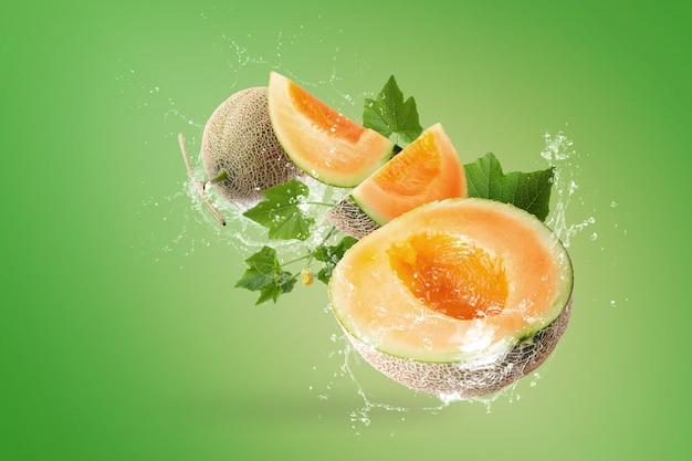 Spruzzi d'acqua su affettato di meloni giapponesi su sfondo verde