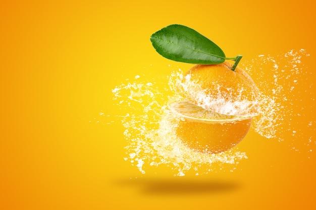 Spruzzi d'acqua su arance fresche a fette e frutta arancione su sfondo arancione
