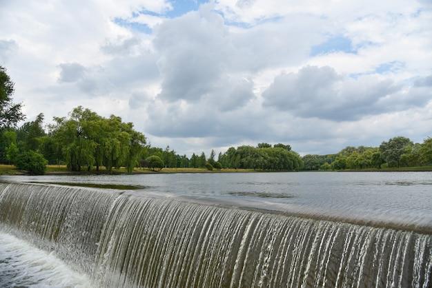 Spruzzi di una cascata su un fiume in un parco cittadino