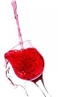 Spruzzi in un bicchiere di vino rosso